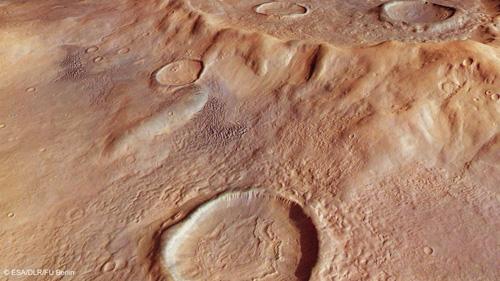 In der Frühzeit des Mars schneite es vermutlich in den Bergen am Westrand von Hellas Planitia. Die Niederschläge verdichteten sich zu Eis, das Gletscher bildete, die unter dem hohen Eigendruck zu fließen begannen und dabei von Staub aus der Atmosphäre, Schutt und Geröll bedeckt wurde. Die trägen Eismassen flossen wie zäher Brei in die Vertiefungen von Kratern und bildeten dort Ablagerungen mit dem hier im Vordergrund erkennbaren eigenartigen Muster, sogenannte konzentrische Kraterfüllungen. In der linken Bildhälfte sind ferner mehrere ausgedehnte, wesentlich jüngere Dünenfelder zu sehen. Image credit: ESA/DLR/FU Berlin