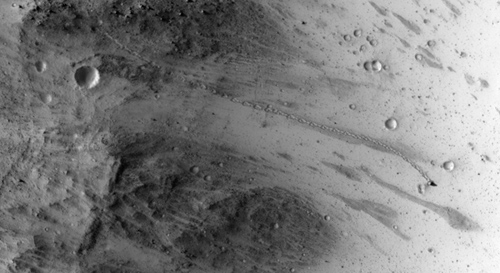The track left by an oblong boulder as it tumbled down a slope on Mars runs from upper left to right center of this image. The boulder came to rest in an upright attitude at the downhill end of the track. The HiRISE camera on NASA's Mars Reconnaissance Orbiter recorded this view on July 3, 2014. Image credit: NASA/JPL-Caltech/Univ. of Arizona