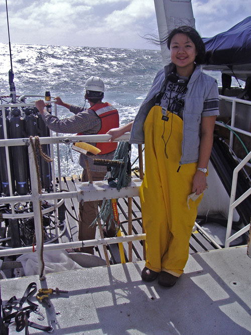 "Li Deng, co-first author on the Nature paper, stands on the deck of the research vessel ""Western Flyer"" in front of the sampling device used to measure salinity, temperature and depth of the ocean during sample collection. (Photo credit: Sullivan lab)"
