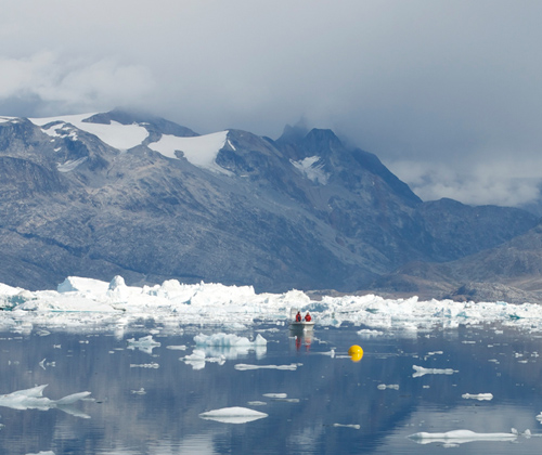 The deployment of a scientific mooring in Sermilik Fjord in August, 2011. The yellow buoyant sphere of the mooring can be seen floating on the surface with authors Rebecca Jackson and David Sutherland in the small boat behind. (Photo by Fiamma Straneo, Woods Hole Oceanographic Institution)