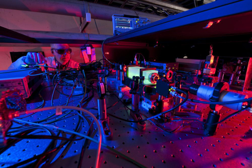 A Fermilab scientist works on the laser beams at the heart of the Holometer experiment. The Holometer will use twin laser interferometers to test whether the universe is a 2-D hologram. Image courtesy of Fermilab