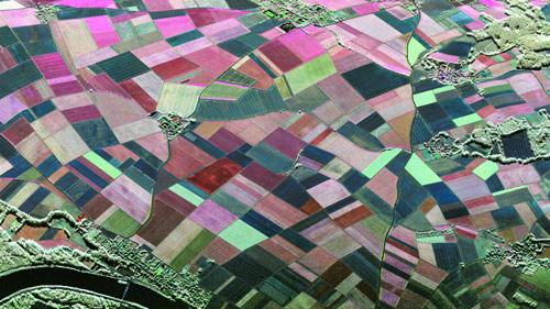 Die Farbkodierung des Radarbilds zeigt die Art der Vegetationsbedeckung und der Bodenbeschaffenheit. Die Farbvielfalt gibt die unterschiedlich starke Rückstreuung des Radarsignals in verschiedenen Polarisationen wieder. Dunkle Farben hingegen markieren glatte und ebene Flächen, da sie das Radarsignal nur schwach reflektieren. So stechen in dieser Aufnahme Straßen als schwarze Linien hervor. Es handelt sich hier um ein voll polarimetrisches RGB-Bild der Testregion Wallerfing, aufgenommen am 12.Mai 2014 im C-Band (5 cm Wellenlänge). Image credit: DLR