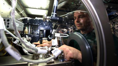 US-Astronaut Reid Wiseman installiert die CCF-Experimentanlage für die vierte Experimentserie in die Microgravity Science Glove Box der ISS. Image credit: NASA