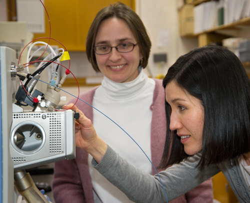 Elizabeth Kujawinski, left, and her colleague Melissa Soule monitor a mass spectrometer. (Photo by Tom Kleindinst, Woods Hole Oceanographic Institution )