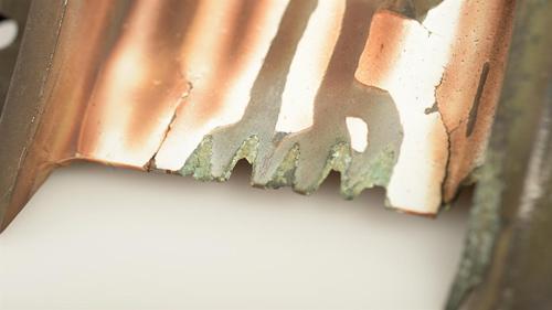 Ähnlich wie bei einem Emaille-Topf, bei dem die kompakte Emaille (Keramik) bei einer Deformation des Topfes abplatzt, platzt eine durch geschmolzene Vulkanasche kompaktierte Wärmedämmschicht von einer Turbinenschaufel ab. Image credit: DLR