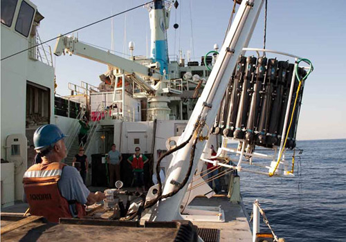 A CTD (conductivity, temperature, depth) rosette is lowered over the side of R/V Knorr during the North Atlantic GEOTRACES cruise in 2011. Data and water samples collected during the cruise contributed to the study of mercury in the global ocean led by Carl Lamborg. (Photo by Brett Longworth, Woods Hole Oceanographic Institution)
