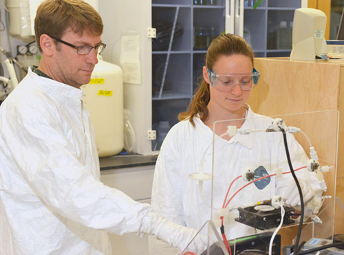 Dr. Carl Lamborg (left), lead author on a recent paper in Nature estimating the amount of natural and pollution-derived mercury in the global ocean with his lab manager, Gretchen Swarr, who is also a co-author on the article. (Photo by Ken Kostel, Woods Hole Oceanographic Institution)