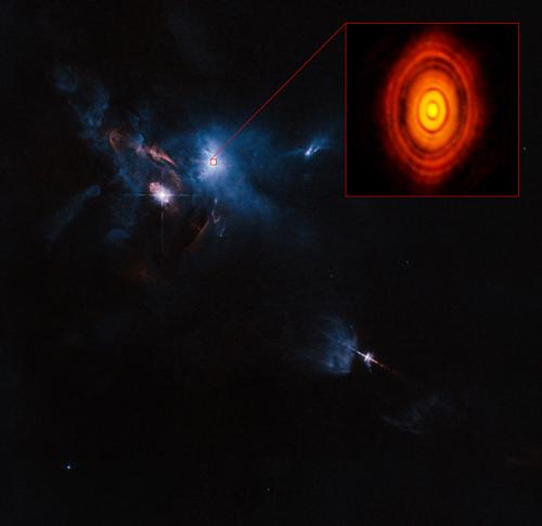 Dies ist eine Kompositaufnahme des jungen Sterns HL Tauri und seiner Umgebung, die Daten von ALMA (vergrößerte Box oben rechts) und des NASA/ESA Hubble Space Telescopes (restliches Bild) verwendet. Es ist die erste Aufnahme von ALMA, in der die Schärfe des Bildes die normalerweise erreichte Schärfe des Hubble-Weltraumteleskops übertrifft. Image credit: ALMA (ESO/NAOJ/NRAO), ESA/Hubble and NASA. Acknowledgement: Judy Schmidt