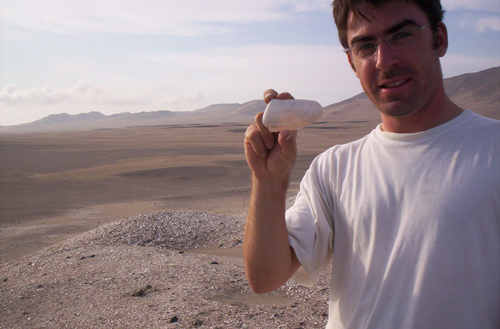 Matthieu Carré holds a 6,800-year-old mollusk collected from a site in Peru's Ica valley. The shells record the temperature of the ocean during their 1- to 3-year lifetime. Image credit: M. Carre / Univ. of Montpellier