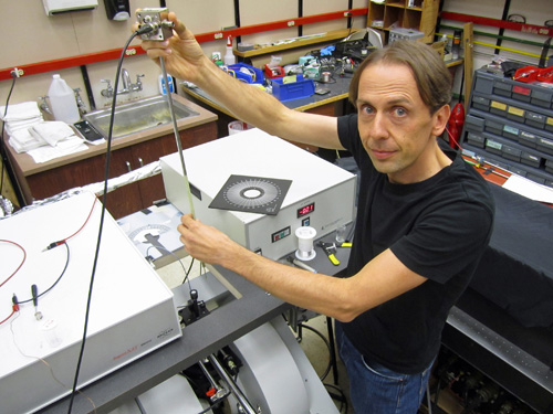 """University of Utah physicist Christoph Boehme works in his laboratory on an apparatus used in a new study that brings physics a step closer to """"spintronic"""" devices such as superfast computers, more compact data storage devices and more efficient organic LEDs or OLEDS than those used today for display screens in cell phones, computers and televisions. The study, published in the Sept. 19 issue of the journal Science, showed the physicists could read the subatomic """"spins"""" in hydrogen nuclei and use the data to control current that powers light in a cheap, plastic LED, or OLED, under practical operating conditions. Photo Credit: Lee J. Siegel, University of Utah"""