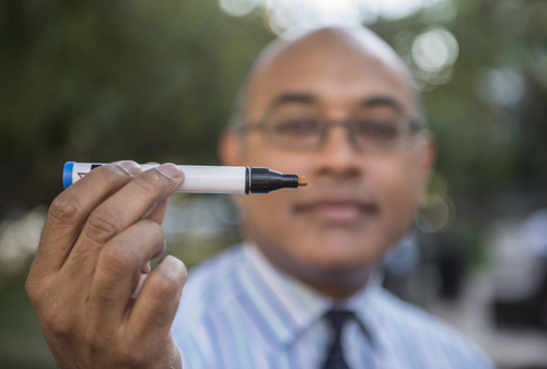 "Assoc. Prof. Jayant Pinto is pictured with a ""Sniffin' Stick,"" an aroma-loaded device used to test patients' ability to identify scents for research on olfactory dysfunction and aging. Photo by Robert Kozloff"