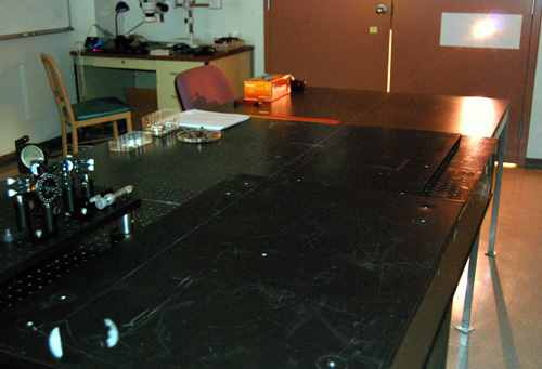In this image, the thin beam of a filament laser is barely visible against the tabletop surface. (Photo by Pavel Polynkin)