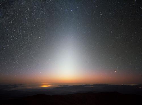Dieses Bild zeigt das Zodiakallicht in seiner vollen Pracht. Man kann es nur  dei dunklem Nachthimmel ohne Lichtverschmutzung und störendes Mondlicht als dreicksförmiges Leuchten sehen. Dieses Foto ist im September 2009 am La Silla-Observatorium der ESO in Chile entstanden, mit Blick Richtung Westen nur wenige Minuten Nach Sonnenuntergang. EIn Wolkenmeer bedeckt das Tal unterhalb von La Silla, das auf einer Höhe von 2400 Metern liegt. Einige kleinere Berggipfel ragen ebenfalls aus dem Dunst. Das Zodiakallicht ist Sonnenlicht, das an Staubpartikeln reflektiert wird, die sich zwischen Erde und Sonne befinden, und kann am besten unmittelbar vor bzw. nach Sonnenauf- bzw. Untergang beobachtet werden. Der Name impliziert bereits, dass das Leuchten immer entlang der Ekliptik auftritt, der scheinbaren Bahn der Sonne am Himmel. damit kommt es automatisch in den Sternbildern des Tierkreises zu liegen, dem Zodiak. Image credit: ESO/Y. Beletsky