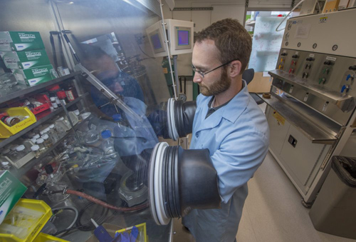 Carter Abney works in a glovebox in the Gordon Center for Integrative Science to handle chemicals that are sensitive to water and air. Abney, a graduate student in chemistry at the University of Chicago, has received a 2014 Innovations in Fuel Cycle Research Award for his work on metal-organic frameworks. Photo by Robert Kozloff
