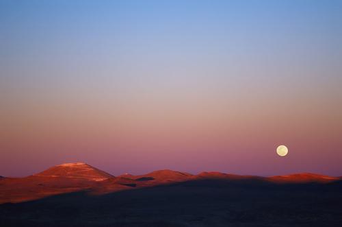 Dieses Bild der zukünftigen Heimat des E-ELT wurde im November 2014 vom nahegelegenen Paranal-Observatorium der ESO aus aufgenommen. Das Abtragen und Einebnen des Gipfels des Cerro Armazones ist bereits weit fortgeschritten (oben links im Bild) und auch die neue breitere Straße, die sich ebenfalls im Bau befindet und sich über das Bild und am Fuß des Berges erstreckt, ist zu erkennen. Zum Zeitpunkt der Aufnahme ging die Sonne über dem Pazifischen Ozean unter und die letzten Sonnenstrahlen streifen den Gipfel des Cerro Armazones. Außerdem ging zur selben Zeit der Vollmond im Osten auf. Image credit: ESO/G. Lambert