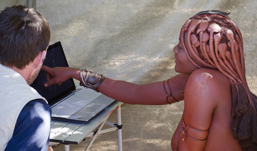 University of Utah anthropologist Layne Vashro with a woman from the Twe tribe in Namibia as she performs a mental rotation task on a laptop computer. It was part of a new study that found evidence men evolved better navigation ability than women because men with better ability to manipulate objects in their mind can roam farther and have children with more mates. Photo Credit: University of Utah