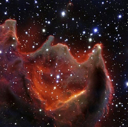 Ähnlich dem gähnenden Maul einer riesigen himmlischen Kreatur leuchtet die kometenartige Globule CG4 bedrohlich in diesem neuen Bild des Very Large Telescopes der ESO. Obwohl es auf der Aufnahme so scheint, als sei sie groß und hell, handelt es sich bei CG4 tatsächlich nur um einen lichtschwachen Nebel, weshalb es sich für Astronomen als schwierig gestaltet, ihn ausfindig zu machen. Die genaue Beschaffenheit von CG4 bleibt allerdings auch weiterhin ein Rätsel. Image credit: ESO
