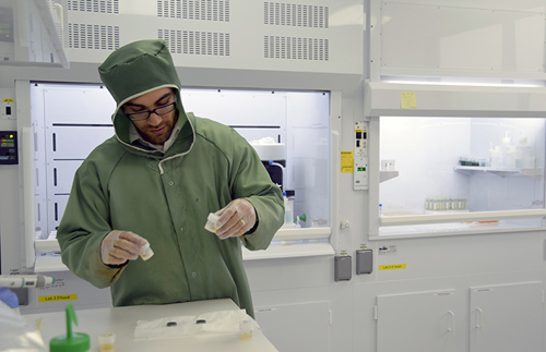 Adam Sarafian, lead author of the paper and a MIT/WHOI Joint Program student in the WHOI Geology and Geophysics Department, preps samples in Sune Nielsen's NIRVANA clean lab to remove all contamination from the surface prior to analysis. (Photo by Jayne Doucette, Woods Hole Oceanographic Institution)