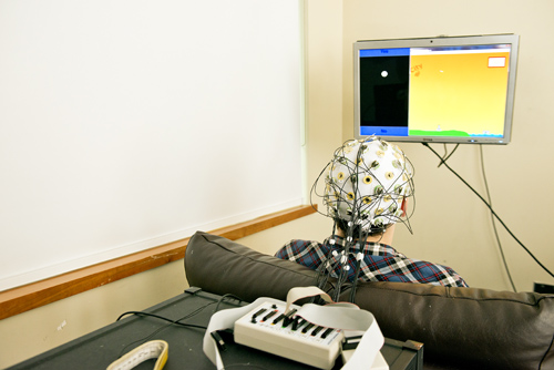 The sender is hooked to an electroencephalography machine that reads brain activity. A computer processes the brain signals and sends electrical pulses via the Web to the receiver across campus.Image credit: Mary Levin, U of Wash.