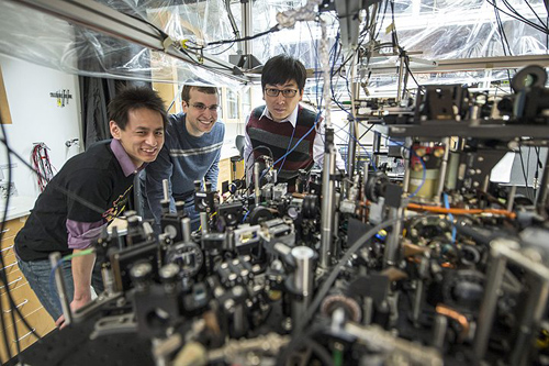 University of Chicago scientists can create an exotic, particle-like excitation called a roton in superfluids with the tabletop apparatus pictured here. Posing left to right are graduate students Li-Chung Ha and Logan Clark, and Prof. Cheng Chin. Photo by Rob Kozloff