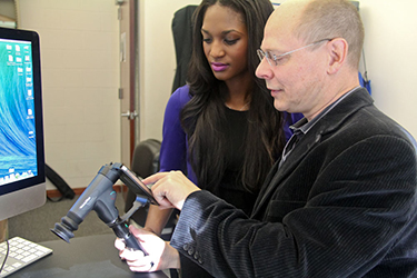 """Biomedical engineering student Jerri-Lynn Kincade and Wolfgang Fink select images of the eye's interior on a smartphone to be sent to a remote """"expert system"""" for subsequent analysis. (Photo credit: Pete Brown/UA College of Engineering)"""