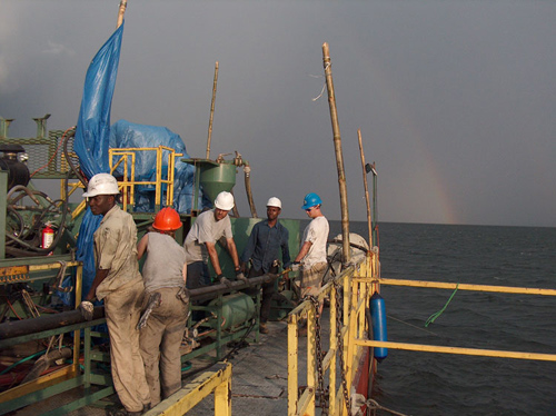 Lead geologist John Peck (U. Akron), far right,  and the team archiving sediment cores aboard the drilling platform on Lake Bosumtwi. (Photo courtesy of Tim Shanahan)