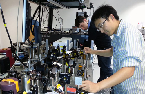 Sam Peng (foreground) and chemistry graduate student Paul Stevenson adjust the two-dimensional infrared spectroscopy system in the laboratory of Prof. Andrei Tokmakoff. Image courtesy of Sam Peng