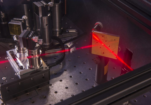 This photograph shows part of the two-dimensional infrared spectroscopy instrument operating in the laboratory of Prof. Andrei Tokmakoff. The normally invisible infrared laser beam appears red in this image with the aid of dry ice. Photo by Robert Kozloff