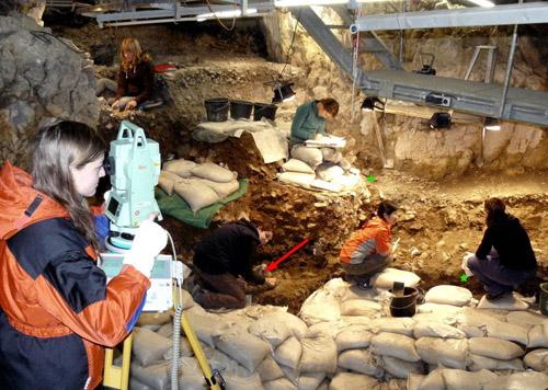 Bild der Grabungen im Hohle Fels von 2008. Der rote Pfeil bezeichnet die Fundstelle der Venus, die beiden grünen Sternchen den Fundort der beiden Teile des neu entdeckten Fragments. Foto credit: M. Malina/Universität Tübingen