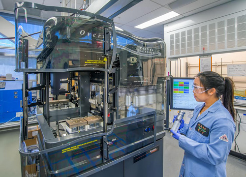 Jessica Su, a UC Berkeley student who worked at the Molecular Foundry with Ron Zuckermann, next to Overture, a robot that assembles dozens of custom peptoids at a time. Image credit: Berkeley Lab