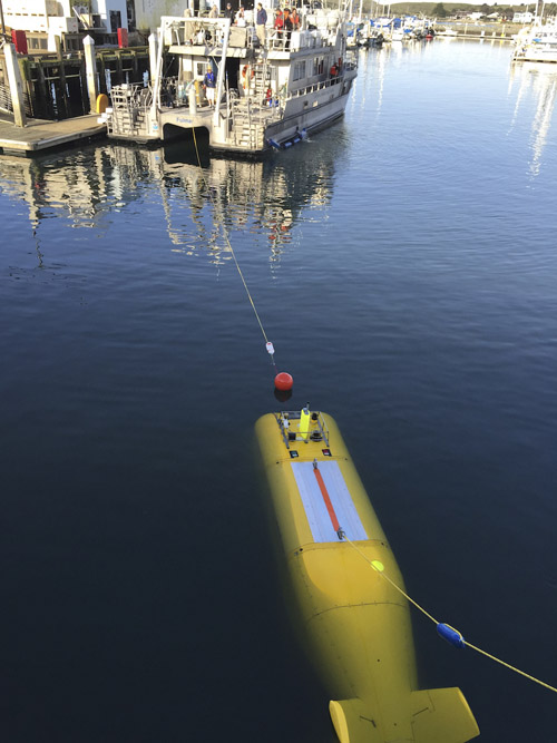 During the 2015 mission to survey the ex-USS Independence CVL 22, the Office of National Marine Sanctuaries' research vessel Fulmar served as the escort boat for Boeing's Autonomous Underwater Vehicle (AUV) Echo Ranger. The 67-foot aluminum catamaran research vessel's crew is preparing to tow Echo Ranger to sea. Image credit: Robert V. Schwemmer, NOAA