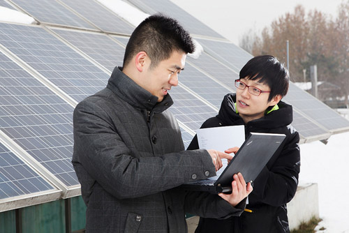 IBM Green Horizons research staff members Dr. Weida Xu and Green Horizons project lead Dr. Jinyan Shao examining a solar panel that supplies daily power to the IBM Research-China Lab. Photo credit: IBM