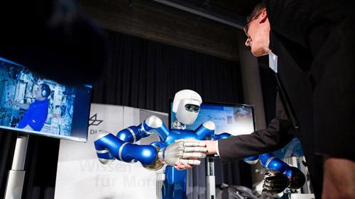 Erster Tele-Handshake mittels eines humanoiden Roboters. Kosmonaut Sergei Volkov an Bord der ISS und DLR-Institutsdirektor Prof. Dr. Alin Albu-Schäffer schütteln sich in Oberpfaffenhofen die Hand - mittels des humanoiden DLR-Roboters SpaceJustin. Am 17. Dezember 2015 wurde erstmals ein humanoider Roboter aus dem Weltall ferngesteuert.Image credit: DLR