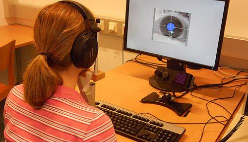 Manuela Marin sitzend vor dem Eyetracker, mit einem Bild ihrer rechten Pupille dargestellt auf dem Bildschirm. (Image copyright: Bruno Gingras)