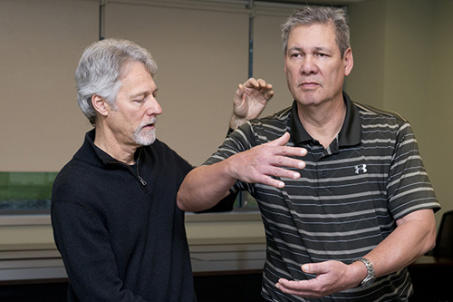 Russ Mason works on form with Scott DeBoda in a tai chi program designed for those with Parkinson's disease. Photo credit: University of Delaware