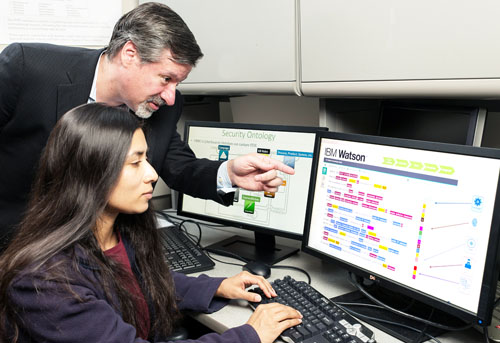 "IBM's Chief Watson Security Architect Jeb Linton demonstrating to University of Maryland Baltimore County student Lisa Mathews how to teach IBM's Watson the language of  security, Tuesday, May 10, 2016, Baltimore, MD. IBM will work with 8 universities to train Watson for Cyber Security, so that the next generation of security professionals can leverage the power of ""cognitive"" technology to defend against cyberattacks.  (Photo credit: Mitro Hood/Feature Photo Service for IBM)"