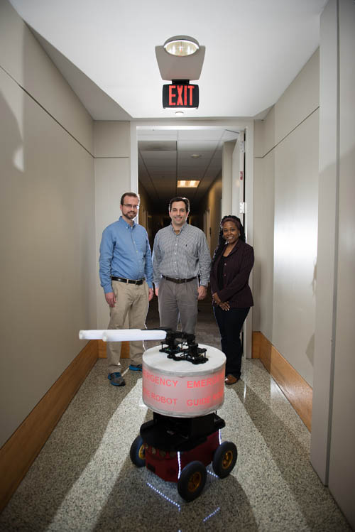 """Georgia Tech researchers shown with their """"Rescue Robot."""" (L-R) GTRI Research Engineer Paul Robinette, GTRI Senior Research Engineer Alan Wagner and School of Electrical and Computer Engineering Professor Ayanna Howard. (Photo credit: Rob Felt, Georgia Tech)"""