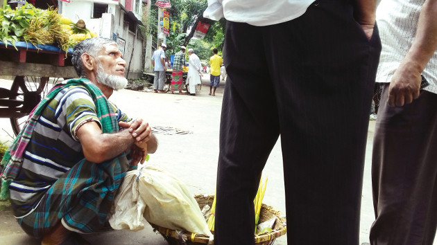 Street hawker Manik Mian bargains with clients to sell his items, which people needs in their daily life. Photo credit: Kayes Sohel