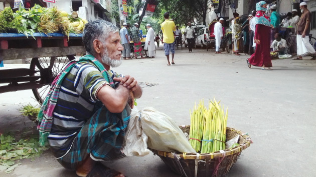 Street hawker Manik Mian waits for customers near a mosque in Dhaka. Photo credit: Kayes Sohel