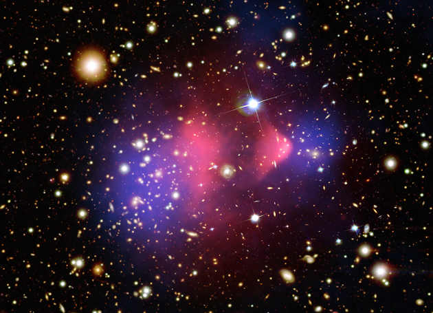 "A composite image of the ""bullet cluster,"" a galaxy cluster formed by a collision of two clusters. The pink clumps show hot gas containing most of the normal matter, while the two blue clumps reveal where most of the mass in the clusters is actually contained. This provides evidence for dark matter since most of the mass was expected to be concentrated around the pink areas. (Image credit: X-ray image by NASA/CXC/M.Markevitch et al.; optical image by NASA/STScI, Magellan/U.Arizona/D.Clowe et al.; lensing map image by NASA/STScI, ESO WFI, Magellan/U.Arizona/D.Clowe et al.)"