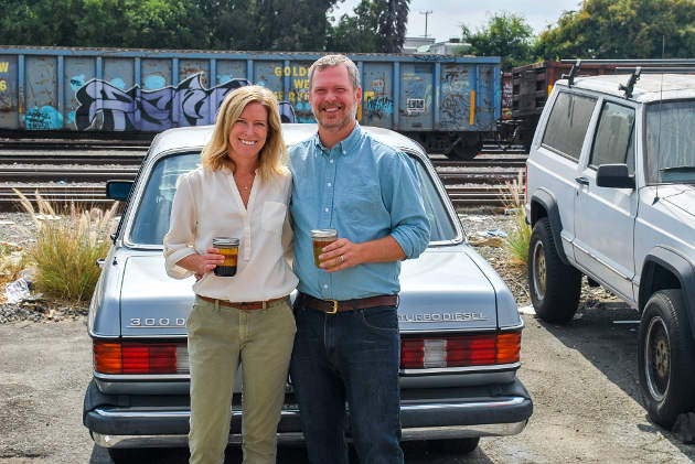 Megan and Marshall Dostal hold jars of grease in front of Marshall's Mercedes 300D, which they power with biodiesel they make. Photo by Michael Cree.