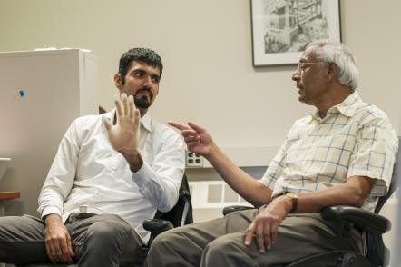 (R-L) MSU Professor Anil Jain and doctoral student Sunpreet Arora demonstrate how a 3-D printed model hand is used to test fingerprint scanners for accuracy. Photo by G.L Kohuth