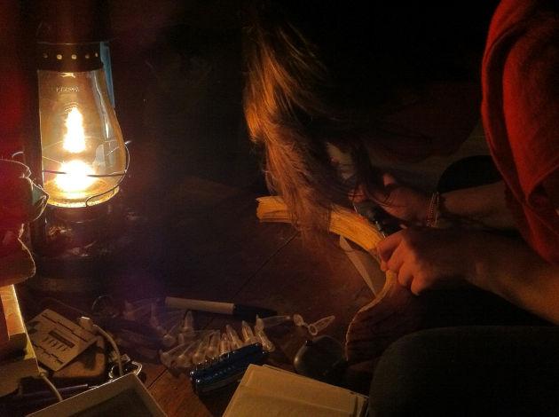 Kendra Chritz sampling hippo canine enamel by kerosene lamplight in Queen Elizabeth National Park. PHOTO CREDIT: Courtesy of Kendra Chritz
