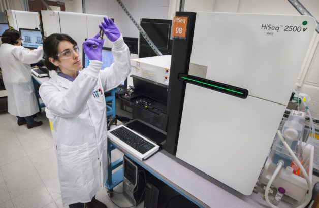 """The microbial DNA samples sourced from the Rifle site were sequenced by the DOE Joint Genome Institute with the """"workhorse"""" Illumina HiSeq platform. Here, JGI scientistJenifer Johnson holds a flowcell.This same process enabled JGI to generate over 141 trillion letters of genetic code in fiscal year 2016 – or the equivalent of 47,000 in human genomes.(Image credit: Berkeley Lab, Roy Kaltschmidt)"""