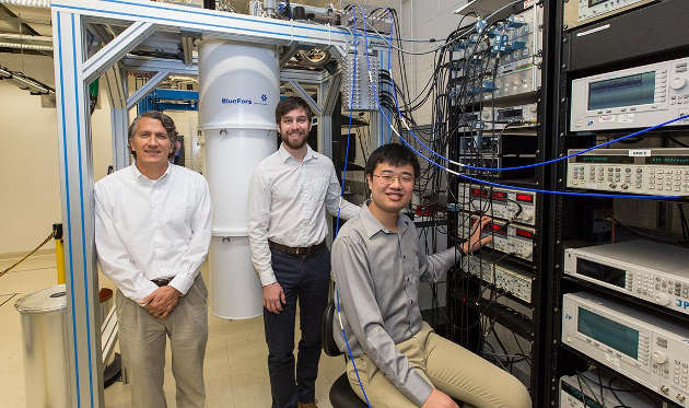 Princeton Professor of Physics Jason Petta, from left, and physics graduate students David Zajac and Xiao Mi, have built a device that is a step forward for silicon-based quantum computers, which when built will be able to solve problems beyond the capabilities of everyday computers. The device isolates an electron so that can pass its quantum information to a photon, which can then act as a messenger to carry the information to other electrons to form the circuits of the computer. (Photo by Denise Applewhite, Office of Communications)