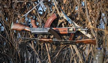 Two rifles belonging to Nyangatom men hang on a brush fence. (Photo by Luke Glowacki)