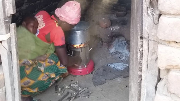 A woman, with sleeping infant on her back, cooking with a forced-draft cookstove in her kitchen in rural Malawi. A traditional cook fire, and the sooty walls that result from its use indoors, are seen in the background. Photo by Andrew Grieshop.
