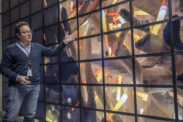 Francesco Panerai of Analytical Mechanical Associates Inc., a materials scientist leading a series of X-ray experiments at Berkeley Lab for NASA Ames Research Center, discusses a 3-D visualization (shown on screens) of a heat shield material's microscopic structure in simulated spacecraft atmospheric entry conditions. The visualization is based on X-ray imaging at Berkeley Lab's Advanced Light Source. (Image credit: Marilyn Chung/Berkeley Lab)