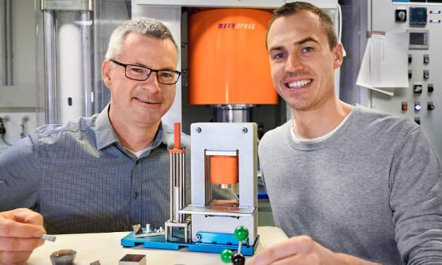 Hubert Huppertz (li.) und Martin Schmitt (re.) mit einem Modell der Hochdruckpresse im Vordergrund. (Image credit: Uni Innsbruck)