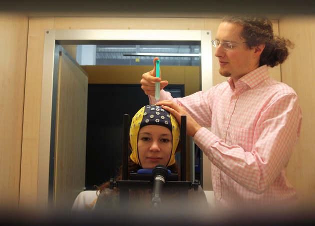 Um eine bessere Übertragungsqualität von Hirnsignalen zu erreichen, tragen die Forscher Kontaktgel auf die Elektroden einer EEG-Kappe auf. Foto credit: Michael Veit